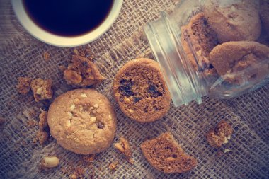 Choccolate chip cookies in glass jar on sack and coffee on wooden table