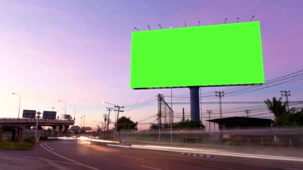 Time Lapse of Blank Billboard egy zöld képernyővel az éjszakai utcában világos nyomvonalakkal