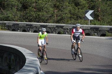 woman and man by road uphill cycling