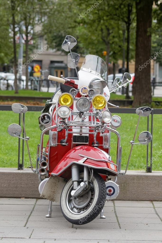 Red retro vespa scooter with many rear-view mirrors and spotligh