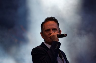 Man in suit and tie singing, smoke in background