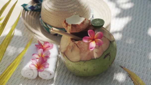 Video footage of green young coconut close up with bamboo straw, sun hat, tropical flowers frangipani, palm shade on white sun bed in Bali