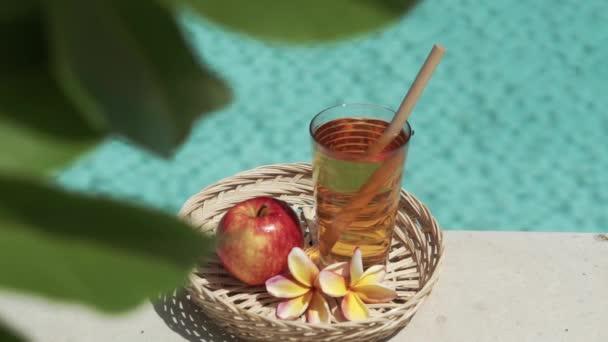 Video záběry ze skla s jablečnou šťávou, bambusovou slámou, červeným jablkem, tropickým květem frangipani, větví stromu se zelenými listy a bublajícím modrým bazénem na pozadí.