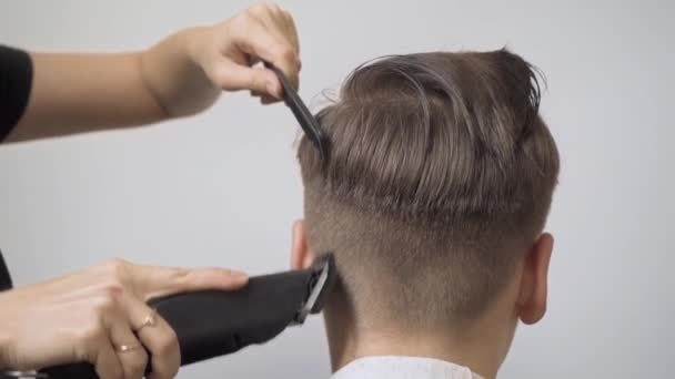 Girl hairdresser cuts the boys hair with a hair clipper on the temples and back of the head.