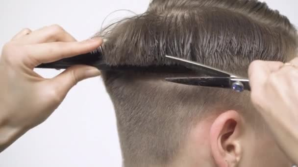 Close-up of hair cutting at the back of the head with scissors and a comb.