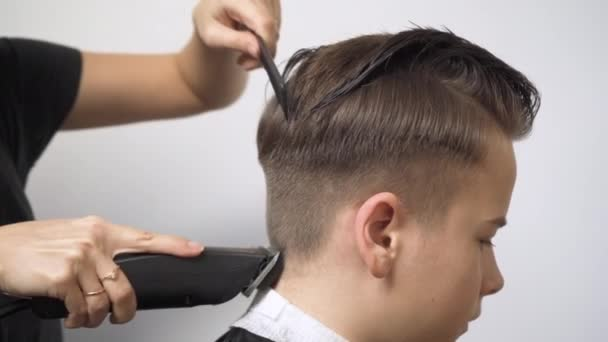 Cutting the hair at the back of the head with a hair clipper.
