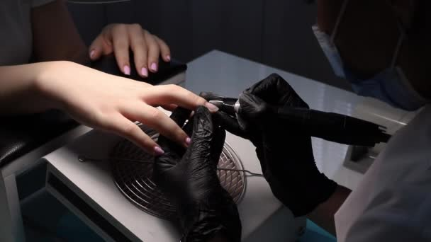 the manicurist polishes the nail in the salon