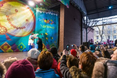 Maslenitsa (pancake week).People looking at the trainer with the bear wich performs on stage.