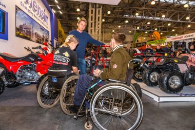 Motopark-2015 (BikePark-2015). Young couple visitors in wheelchairs looking exhibition stand with motorcycles and ATVs.