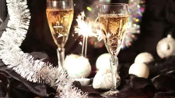 Pezsgő bugyog a pohárban. Sparkler ég. Két pohár pezsgő, bengáli fény és karácsonyi dekoráció. Üdülési hangulat. Nem fókuszált háttérrel. Boldog karácsonyt és boldog új évet!!