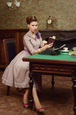 Pin Up beautiful young woman in vintage interior reading a book and prints on an old typewriter