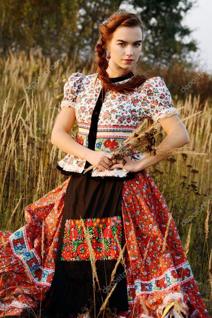 Young peasant woman, dressed in Hungarian national costume, posing over nature background