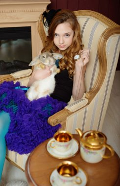 Young girl in the image of Alice in Wonderland is sitting in a chair by the fire, holds a rabbit and a pocket watches