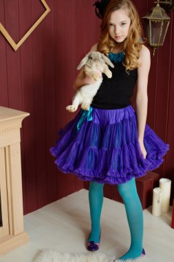 A young girl in the image of Alice in Wonderland stands near the fireplace and holds a rabbit