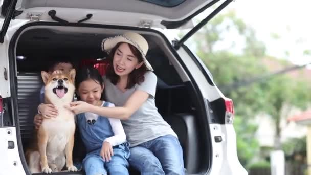 Happy family getting ready for road trip on a holiday. Happy asian children and Mother with shiba inu sitting and Sing Song in car.