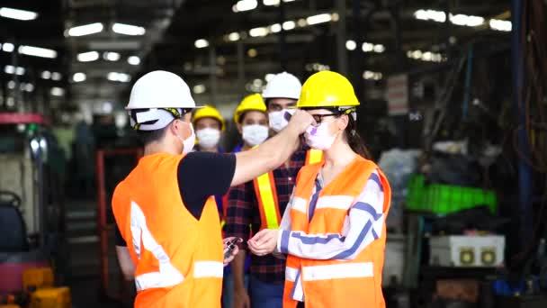 A gyári dolgozók mérik a hőmérsékletet, hogy szűrjék a vírussal fertőzött embereket. Ipari üzemekben