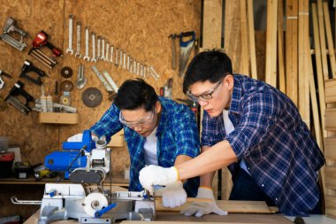 Two carpenters are working in a wood factory. The carpenter is sketching the wood. Concentrated man cutting wooden.