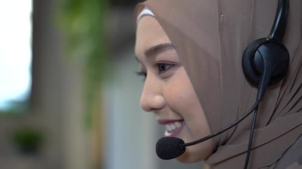 Muslim call center staff. The young call center is working to answer customer questions. Young female customer support executive working in office.