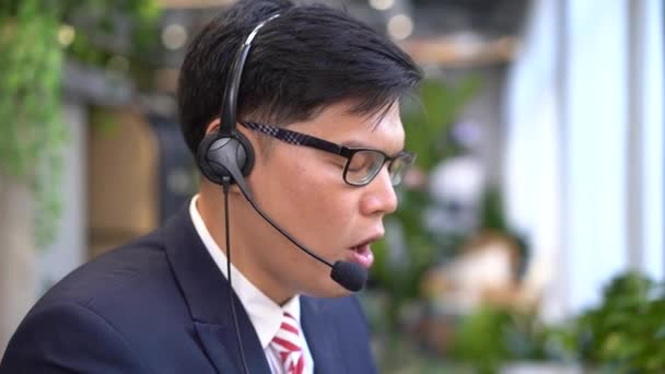 The young call center is working to answer customer questions. Young male customer support executive working in office.