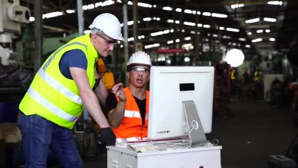 Výrobní průmysl s technologií. Inženýři a technici pracují na průmyslových počítačích. Inženýr manažer příkaz počítač vyrábět produkty pomocí automatizovaných strojů v továrně dílny.
