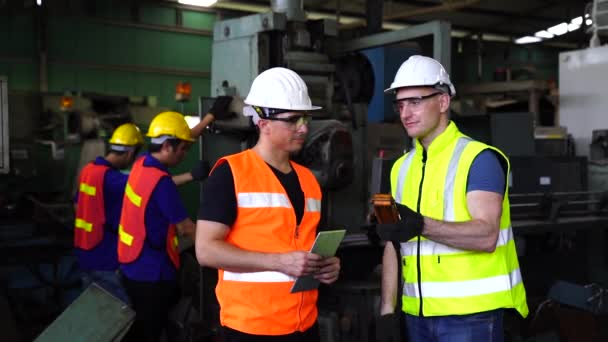 Arbeiter in einer Fabrik drücken einen Knopf aus einer Maschine. Techniker steuern den Betrieb der Maschine mit dem Tablet-Computer.