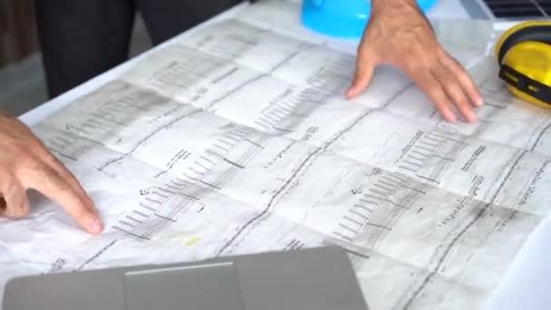 Geschäftsmann und Ingenieur Hand Drawing Plan On Blue Print mit Architektenausrüstung diskutieren die Grundrisse über Baupläne auf dem Tisch.
