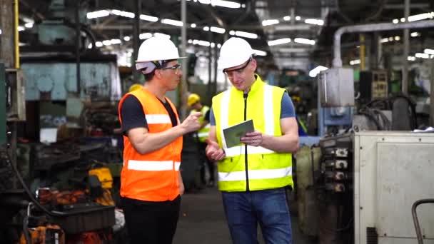 Průmysloví pracovníci a inženýři ovládají stroje s tabletami a počítači. Skupina profesionálních techniků a inženýrů v ochranných oděvech pracuje v průmyslových závodech.