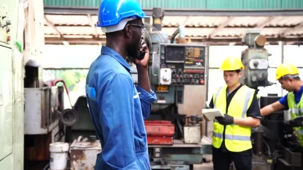 Inženýři a zkušení technici udržují stroje. Profesionální technici drží tablet pro řízení prací v průmyslových závodech.