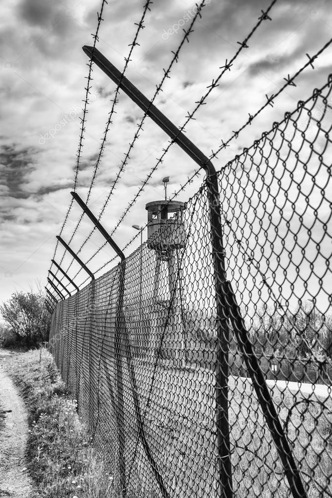 Abandoned sentry box tower isolated by a net with barbed wire ...