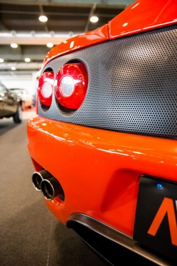 exhaust pipes and tail lights of an orange sports car