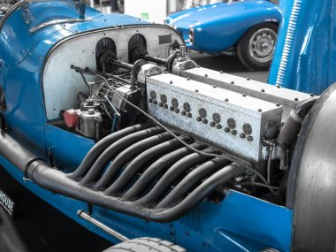 Detail of the engine and exhaust pipes of a vintage racing car.