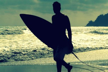 Silhouette of surfer with a board on a sunset evening in Manuel Antonio's National Park main beach, Costa Rica