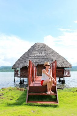 Young beautiful woman enjoying her time and resting close to the sea in Yandup lodge's private cabins, Yandup Island, San Blas, Panama