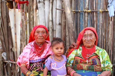 Playón Chico village, Panama - August, 4, 2014: Three generations of kuna indian women in native attire sell handcraft clothes to travelers, San Blas region, Panama.