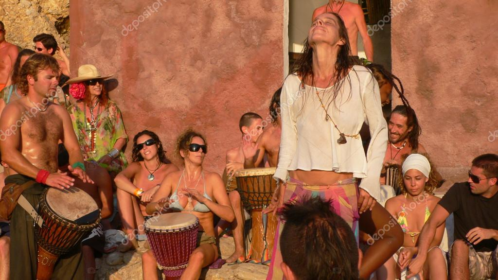 Benirras beach, Ibiza, Spain - July 23, 2006: Lots of people watching the sunset while playing drums and other instruments. This traditional celebration takes place all Sundays of July and August.