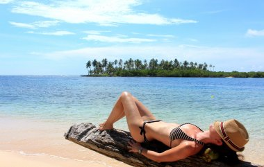 Young beautiful woman enjoying her time and resting close to the sea in the southern beach of