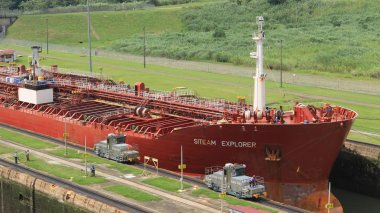 Red large cargo ship entering Miraflores Locks