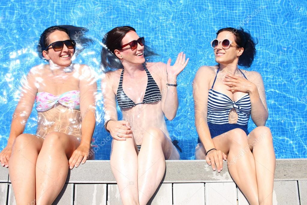Three cheerful young women simulate that they sit over a pools edge with a water wall backwards.