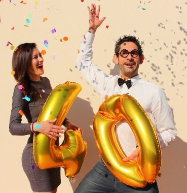 Cheerful couple celebrates a forty years birthday with big golden balloons and colorful little pieces of paper in the air.
