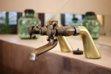 Detail of a vintage faucet placed in the bathroom of a luxury room in a country cottage hotel close to Girona, Catalonia, Spain.