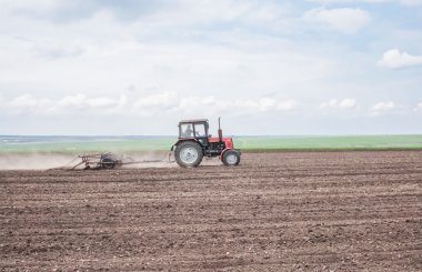 Ukraine, Dnepropetrovsk region. Tractor tilling a field for sowing wheat. The photo shows a field, and the fertile soil