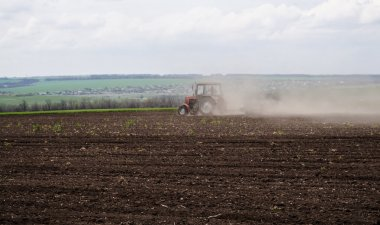 Ukraine, a ploughed field and a tractor in the dust