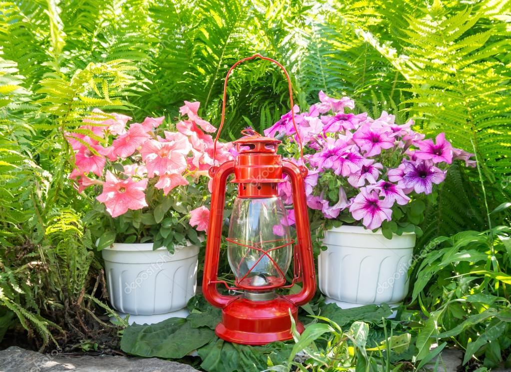 Old kerosene lamp and petunias in the garden