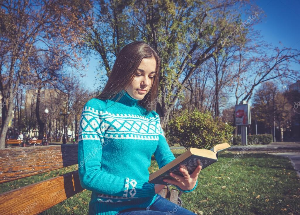 The girl in the blue sweater and fascinating book — Stock Photo ...