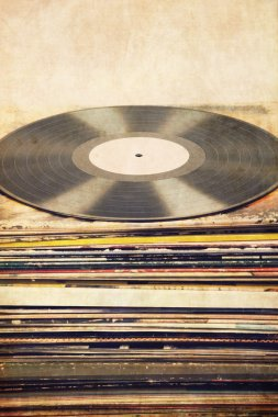 Vinyl record on a tower of album covers, textured, vintage, retro