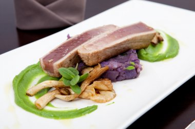 Seafood dinner with fillet of tuna, green pea puree, oyster mushrooms, and potatoes
