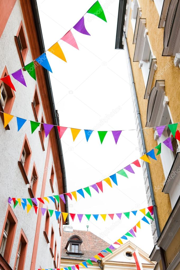 colorful pennants on ropes hanging on house facades