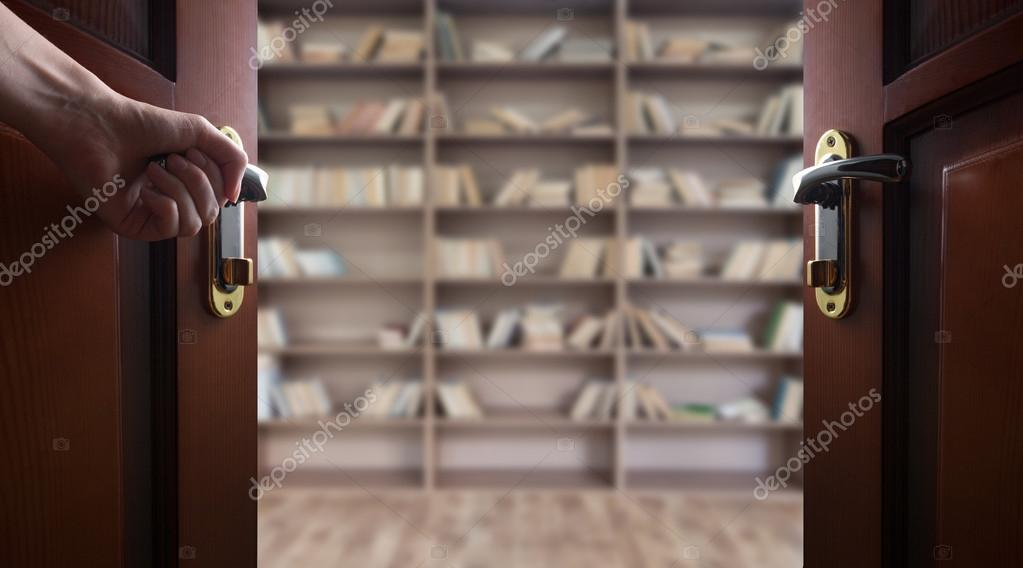 De Bibliotheek Kamer : Hand opent kamer deur naar de bibliotheek van het boek u stockfoto