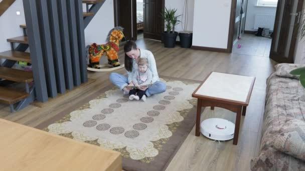 Robot vysavač úklid v obývacím pokoji, zatímco matka a dítě hraje uvnitř. Automatický vysavač