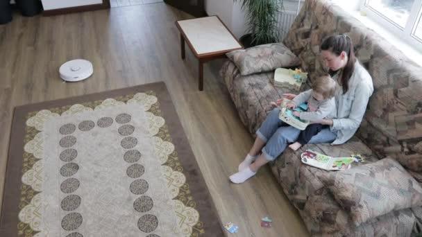 Robot porszívó takarítás a nappaliban, míg anya és a gyermek játszik zárt térben. Automata porszívó